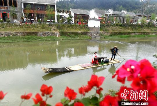 在福州市永泰县嵩口镇月洲村的桃花溪上,身着汉服的古筝师弹着乐曲乘着小船缓缓行来。 吕明 摄