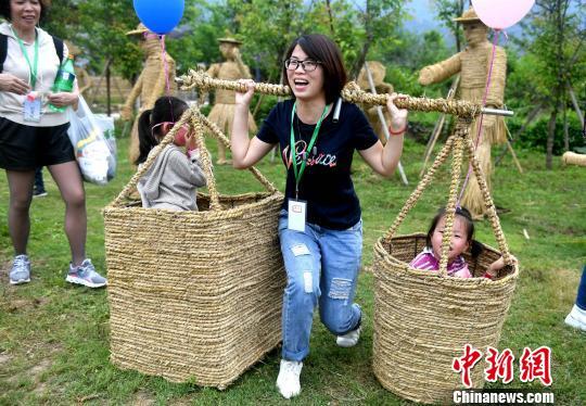 """游客在""""创意稻草部落""""打卡,体验农耕的乐趣。 吕明 摄"""